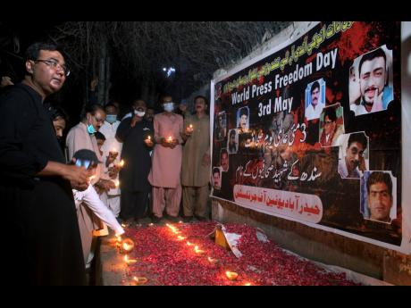 Members of the media place clay lamps in front of a banner with the pictures of killed journalists during a vigil to pay tribute to  them on the eve of World Press Freedom Day in Hyderabad, Pakistan, on Monday. A committee of journalists in Pakistan said t