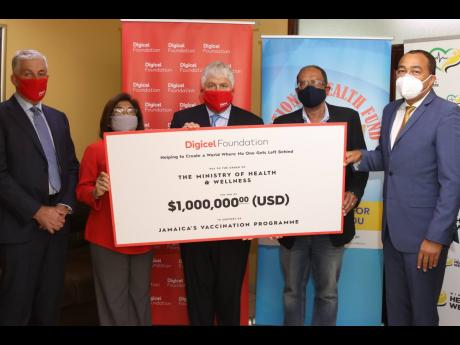 Denis O'Brien (centre), chairman of Digicel and patron of the Digicel Foundation, hands over a symbolic cheque for US$1 million to Dr Christopher Tufton (right), Minister of Health and Wellness and Howard Mitchell (second right), chairman of the National
