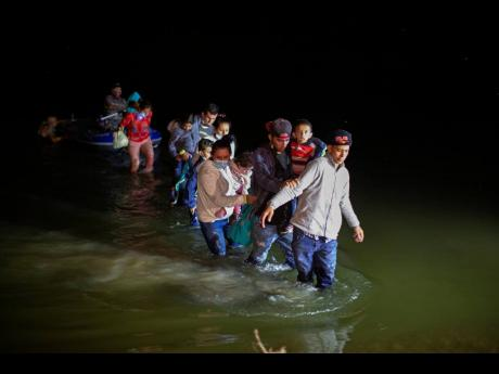 In this March 24 photo, migrant families, mostly from Central American countries, wade through shallow waters after being delivered by smugglers on small inflatable rafts on US soil in Roma, Texas.