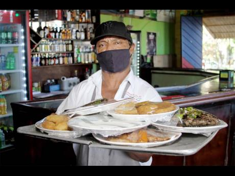 A staff member at Little Ochie Seafood Restaurant and Bar prepares to serve customers.