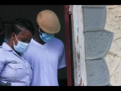 Anthony Bailey, ex-partner who allegedly stabbed 23-year-old Stephina Ralston in Warsop, Trelawny, leaves the Trelawny Parish Court alongside a policewoman on Monday. Bailey has not yet retained a lawyer.