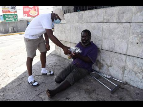 Winston May-Hew, director of Righteousness Promotions, hands out a care package to Aljoe, a homeless man, in Half-Way Tree on Sunday.