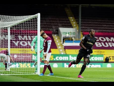 West Ham's Michail Antonio (right) celebrates after scoring his side's first goal during their English Premier League match against Burnley at Turf Moor Stadium in Burnley, England yesterday.