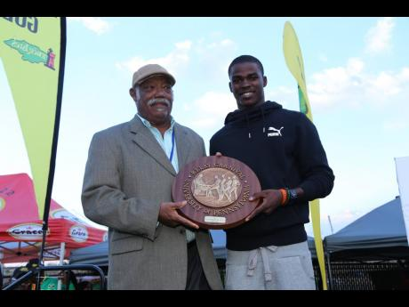 Jamaican track and field icon and Olympian Dr Dennis Johnson (left) poses with young Jamaican sprinter Michael O'Hara at the Penn Relays in 2014.