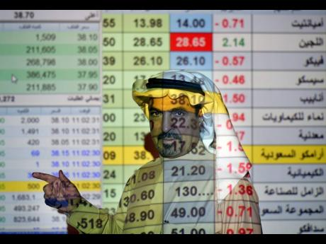 A trader talks to others in front of a screen displaying Saudi stock market values at the Arab National Bank in Riyadh, Saudi Arabia, on December 12, 2019.