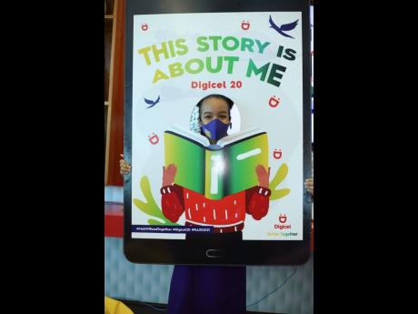 A student cathes a reading-themed photo op during the Digicel  'Mek Wi Read Together' event.