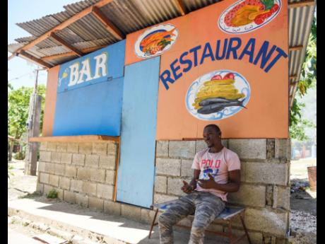 Tyron Wilson sits in front of his food shop near the Caymanas River on Tuesday, May 4. COVID-19 protocols have caused a lockdown of dozens of rivers and beaches across Jamaica.
