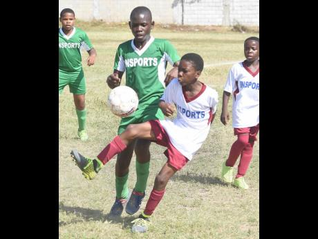 Kimani Reece (right) of York Town brings the ball under control while under pressure from Chadwick Thomas of St Benedict's in their INSPORTS All-Island Primary School Football quarter-final first leg tie at the Bell Chung Oval on January 28, 2019. The ga