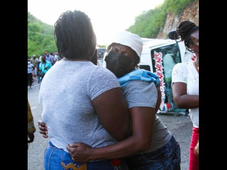 Lorna Ellis, mother of Hector Mowen, the taxi driver who perished in a three-vehicle collision on the Chapelton main road on Tuesday, is comforted by a friend on Tuesday.