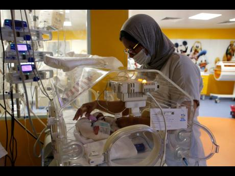 A Moroccan nurse takes care of one of the nine babies protected in an incubator at the maternity ward of the private clinic of Ain Borja in Casablanca, Morocco, yesterday.