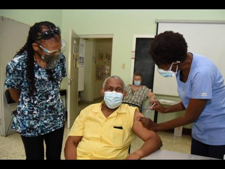 Professor Howard Spencer is vaccinated with his second dose of the Oxford-AstraZeneca vaccine by Dr Kayon Donaldson Davis at the Mona Ageing and Wellness Centre on Wednesday while his wife, Beverley Spencer, looks on. He was among the first set of persons