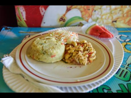 The ackee and salt fish and mashed sweet potato is served with raw vegetables and two slices of melon.