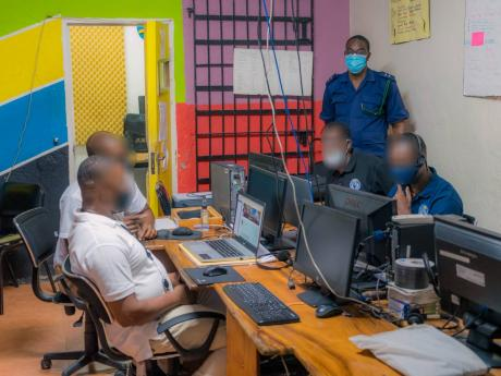 Staff Officer Peter Jarrett monitors the four inmates currently enrolled at the University of Commonwealth Caribbean as they participate in an online class from the St Catherine Adult Correctional Centre computer lab.