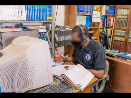 One of the inmates currently enrolled at the University of the Commonwealth Caribbean completes an assignment at the St Catherine Adult Correctional Centre school library.