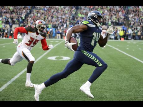 Seattle Seahawks wide receiver DK Metcalf (right) runs to score a touchdown ahead of Tampa Bay Buccaneers defensive back Jamel Dean during the second half of a NFL football game in Seattle, on Sunday, November 3, 2019.