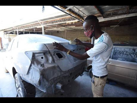 Jerome Bryson, a beneficiary of the Possibilities Programme, works on getting the body of a car smooth for spraying at Den-All auto body repair shop.