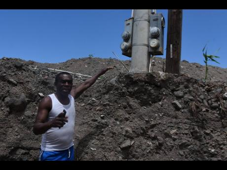 Fitzroy Lovelace, a resident from Weise Road in Bull Bay, St Andrew, shows a light post still covered in silt months after the devastating floods in the area last year.