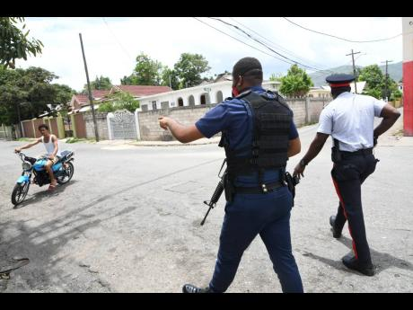 Policemen beckon to a motorcyclist to stop near a state-of-emergency checkpoint in central Kingston on Sunday, June 14, 2020.