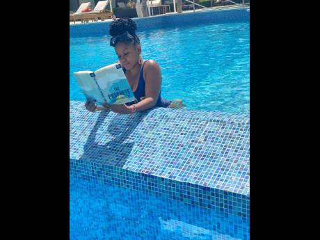 Shanique Sinclair makes it a point of duty to catch up on some light reading, even while lounging in the pool.