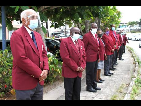 Justices of the Peace line the sidewalk on Caledonia main road, Mandeville to bid farewell to former custos of Manchester, Dr Gilbert Allen.