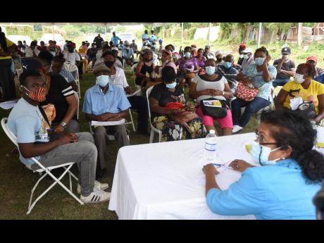Health workers and  hundreds of persons wait at the Old Harbour Civic Centre, St Catherine, for the arrival of vaccines last month.