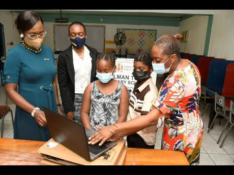 La-Toya Nesbitt (right), principal of Allman Town Primary School, tries out one of the laptops that were presented to the students by JN Fund Managers while her students Jhemeilia Gentles (centre) and Emilio Kongal look on. The laptops were presented by De