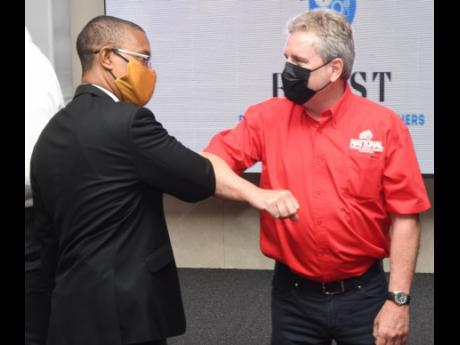 Cementing the partnership: Dr André Coy, associate dean in the Faculty of Science and Technology, UWI, Mona campus (left), greets Brian Jardim, chairman of the National Baking Company Foundation, with an elbow bump.