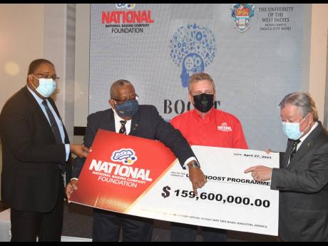 Professor Dale Webber, pro-vice-chancellor and principal, UWI, Mona campus (second right), and chairman and CEO of National Baking Company and patron Gary 'Butch' Hendrickson point to the cheque for $159.6 million presented by the foundation at the lau