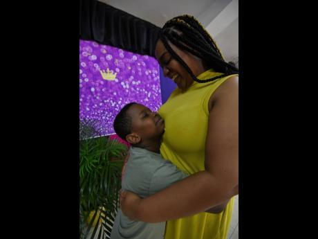 Nathaniel Morgan gives mom Letesha Roberts-Morgan a hug at Waltham Park New Testament Church of God on Thursday.
