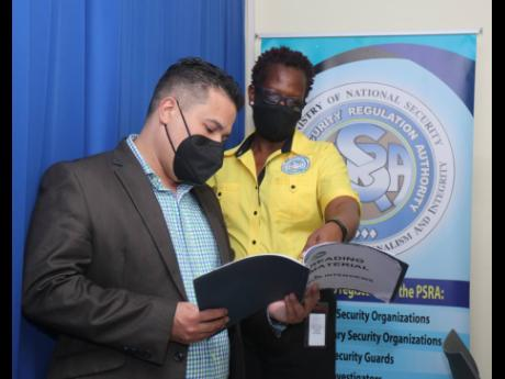 Senator Matthew Samuda, minister without portfolio in the Ministry of National Security, and Vivette Webber McLaughlin, operations manager of the western regional branch of the Private Security Regulations Authority in Montego Bay, St James, look through a