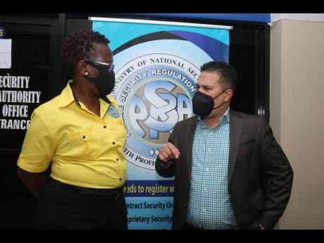 Senator Matthew Samuda, minister without portfolio in the Ministry of National Security, talks with Vivette Webber-McLaughlin, operations manager of the Private Security Regulations Authority in Montego Bay, in Montego Bay on Thursday.