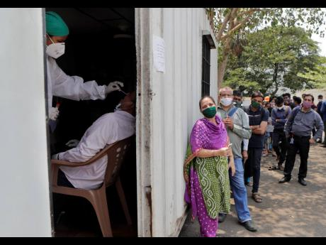 A health worker takes a nasal swab sample of a person to test for COVID-19 as others wait for their turn outside of a field hospital in Mumbai, India, yesterday.