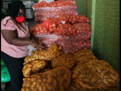 Proprietor of Quality Grains, Sylvia Tomlinson-Hird, proudly points out that this batch of Irish potatoes in her warehouse at 99 Newport Boulevard, St Andrew, is a locally grown Spunta variety. The farmer and importer operates a 305-acre farm in St Ann whe