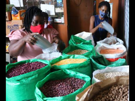 Proprietor of Quality Grains, Sylvia Tomlinson-Hird (left), steps in to serve a customer during a busy period at her business place at 99 Newport Boulevard, St Andrew, on Thursday.