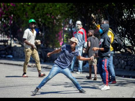 In this February 2021 photograph, a demonstrator throws rocks at the police during a protest to demand the resignation of Haitian President Jovenel Moise in Port-au-Prince, Haiti.