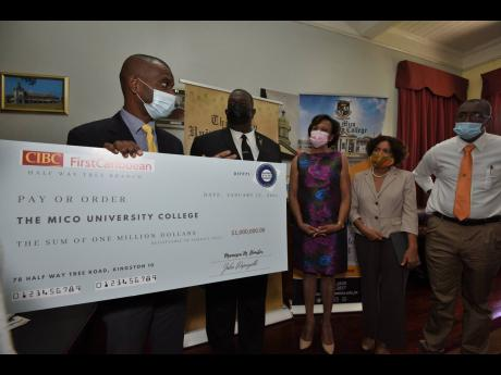 Dr Ashburn Pinnock (left), president of The Mico University College, thanks members of Mico's Batch #146 alumni after they presented a cheque for $1 million to assist needy students at the college. The members are, from right:  Everaldo Orr; Sharon Wolfe