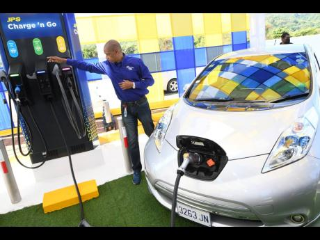 Richard Gordon, manager, business development at JPS explains how the electric vehicle charging station works yesterday when the company commissioned its first public electric vehicle charging station at Boot Service Station, Drax Hall, in St Ann on Friday