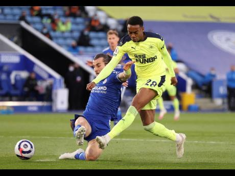 Newcastle's Joe Willock (right) is challenged for the ball by Leicester City's Çağlar Söyüncü during their English Premier League match at the King Power Stadium in Leicester, England yesterday.