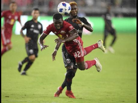 In this file photo from July 2018, Kemar Lawrence (front), then of New York Red Bulls, gets airborne while challenged by then DC United defender Oniel Fisher, Lawrence's national teammate, during the first half of a Major League Soccer match in Washingto