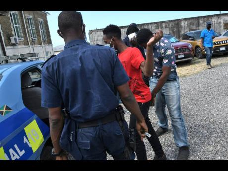Police officers escort three of five persons accused in a buggery case now before the St Ann Parish Court. When they appeared in court yesterday a new date was set for hearing on May 14.