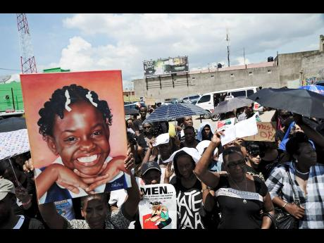 In this 2008 photograph a protester holds up a poster of Ananda Dean, a 11-year-old who was sexually abused and killed. Violence against children is a major concern in Jamaica, with critics saying that the country has failed the children and much more nee