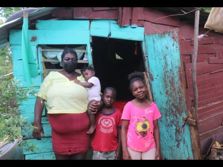 Topal Williams and three of her children stand outside their home in Schoolfield, St Elizabeth.