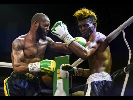 Edmund Declou (right) grimaces in reaction to a left hook from two-time Contender Series winner Sakima 'Mr Smooth' Mullings, during a bout at the National Arena on Friday, March 16, 2018.