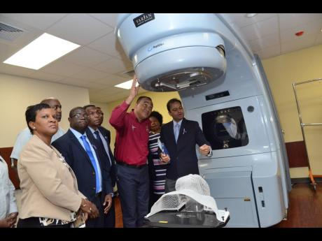 Health and Wellness Minister Dr Christopher Tufton (second right) and other officials examine the LINAC machine at the opening of National Cancer Treatment Centre at St Joseph's Hospital on Monday, November 26, 2018.