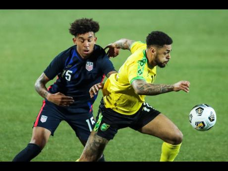 USA's Chris Richard, (left) duels for the ball with Jamaica's Andre Gray during the international friendly match between USA and Jamaica at SC Wiener Neustadt stadium in Wiener Neustadt, Austria, Thursday, March 25, 2021.