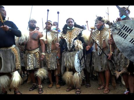 Prince Misuzulu Zulu (centre), flanked by fellow warriors in traditional dress during a ceremony in Nongoma on Friday May 7, 2021. A new Zulu king in South Africa has been named amid scenes of chaos as other members of the royal family questioned Prince M