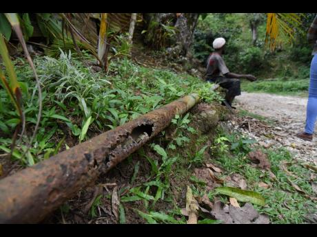 A rusted pipe in Mendez, Gully Road, St Catherine, is a makeshift seat used by residents of the community.