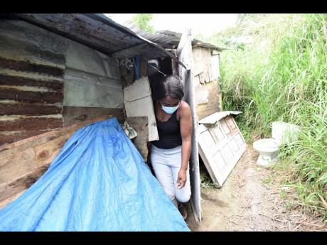 Janet McKenzie emerges from the two-room shack she calls home for two of her four children in Green Peas district, Content Gap.