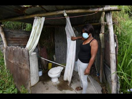Janet McKenzie shows the makeshift bathroom near the ramshackle place she calls home in Green Peas, Content Gap.