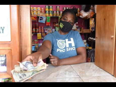 Michelle Swearing, shopkeeper at Top Road in Mavis Bank, hands change to a customer on the weekend. She says that transportation costs linked to the Gordon Town road breakaway have had to be passed on to customers.